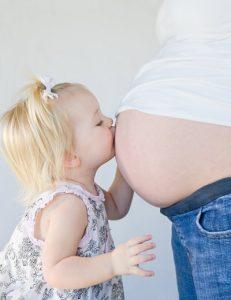 petite fille embrassant ventre de femme enceinte